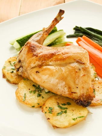 Plate with roasted rabbit leg and vegetable garnish. Shallow dof. photo