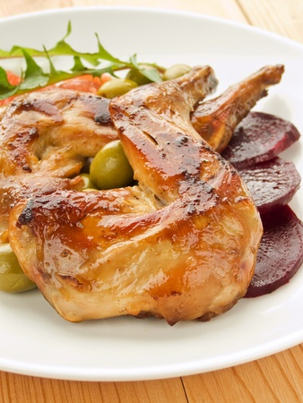 Plate with roasted rabbit legs and vegetable garnish. Shallow dof. photo