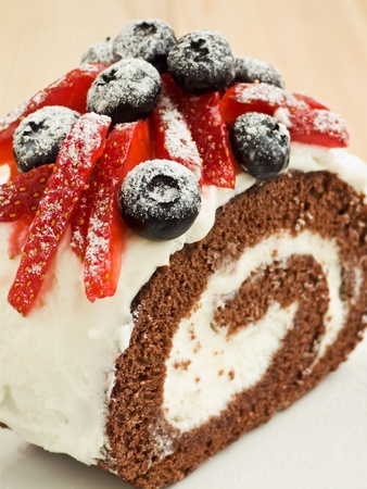 chocolate covered strawberries: Strawberry-blueberry roulade with whipped sour cream. Shallow dof. Stock Photo