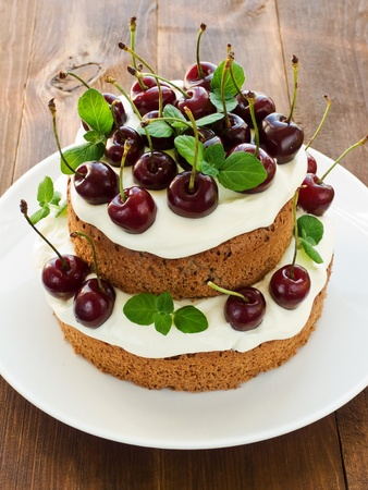 Cake with sweet cherries and whipped sour cream. Shallow dof. Stock Photo