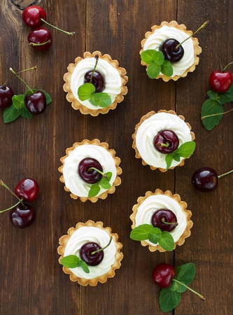Tartlets with sweet cherries, whipped sour cream and mint. Viewed from above. photo