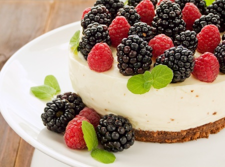 Sour cream cheesecake with raspberries and blackberries. Shallow dof.
