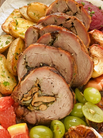 Roasted turkey roulade with potatoes, beet and fruits. Shallow dof. photo
