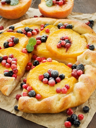 baked treat: Homemade tart with peaches and berries. Shallow dof. Stock Photo