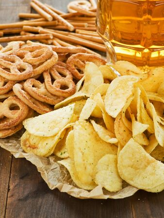 Beer with pretzels, saltsticks and potato chips. Shallow dof. photo