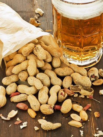 Beer and peanuts on the wooden background. Viewed from above. Stock Photo - 10667370