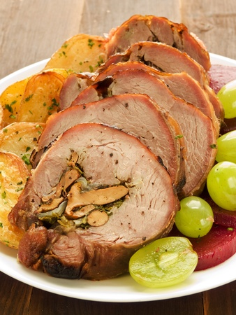 Roasted turkey roulade with potatoes, beet and grapes. Shallow dof. photo