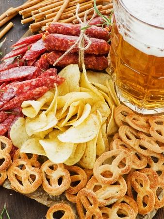 Beer with wienerwurst, pretzels, saltsticks and potato chips. Viewed from above. Stock Photo