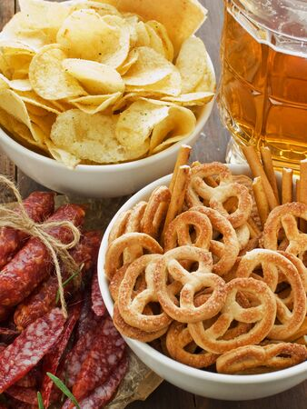Beer, wienerwurst and bowls with chips and pretzels. Viewed from above. photo