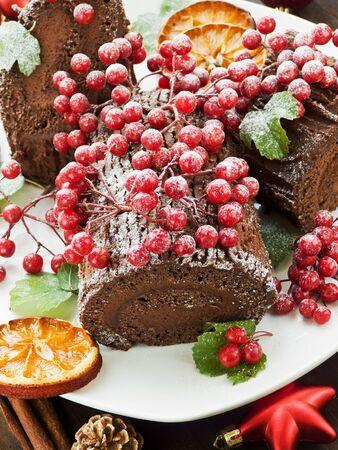 Homemade christmas chocolate yule log with wild berries. Shallow dof. photo