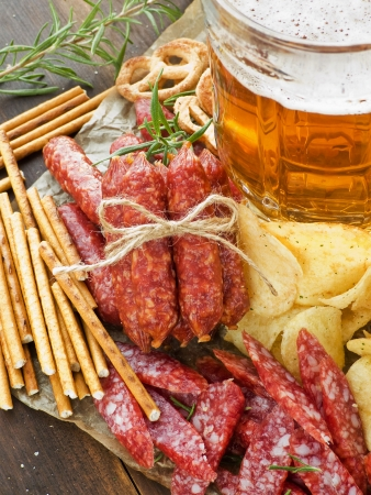 german alcohol: Beer with wienerwurst, pretzels, saltsticks and potato chips. Viewed from above. Stock Photo