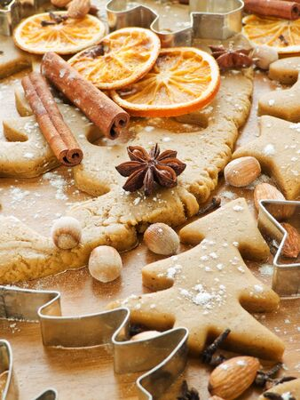 gingerbread man: Christmas baking background dough, cookie cutters, spices and nuts. Viewed from above.