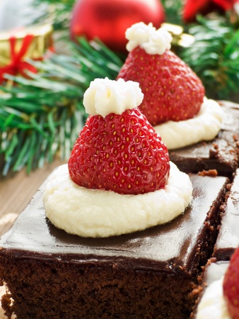 cioccolato natale: Santa Hat brownie morde sullo sfondo di legno. Dof poco profondo.