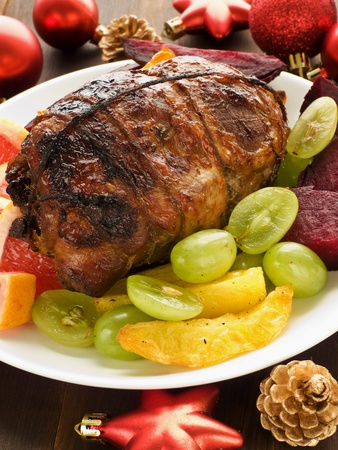 Christmas dinner turkey roulade with fruits and vegetables. Shallow dof. photo