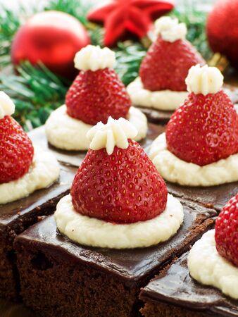 weihnachtskuchen: Weihnachtsmütze brownie beißt auf dem hölzernen Hintergrund. Shallow dof.