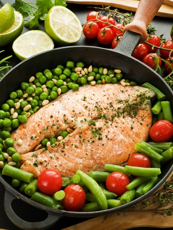 Frying pan with salmon steak, stir-fry veggies and herbs. Viewed from above. Stock Photo - 12433552