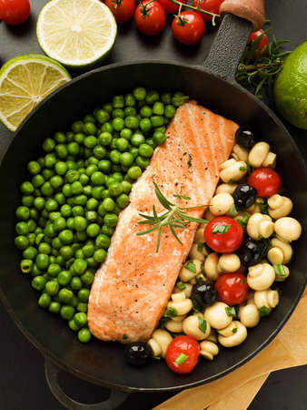 Frying pan with salmon steak, stir-fry veggies and herbs. Viewed from above. Stock Photo - 12527675
