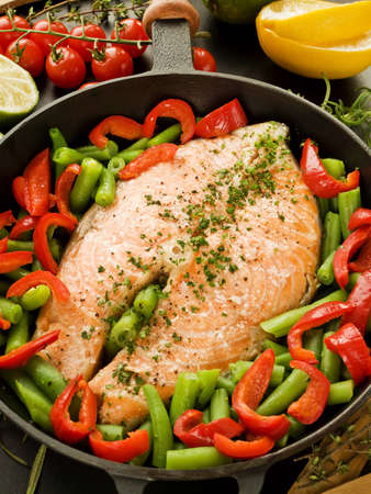 Frying pan with salmon steak, stir-fry veggies and herbs. Viewed from above. Stock Photo - 12527677