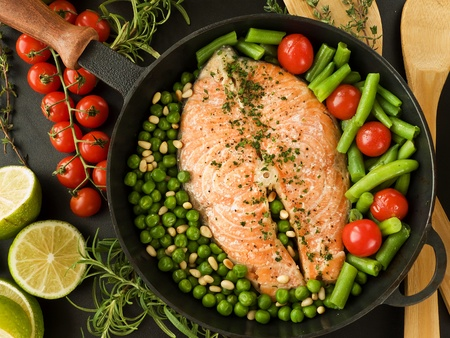 Frying pan with salmon steak, stir-fry veggies and herbs. Viewed from above. photo