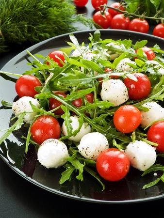 Fresh salad with cherry tomatoes, rucola and mozzarella. Shallow dof. photo