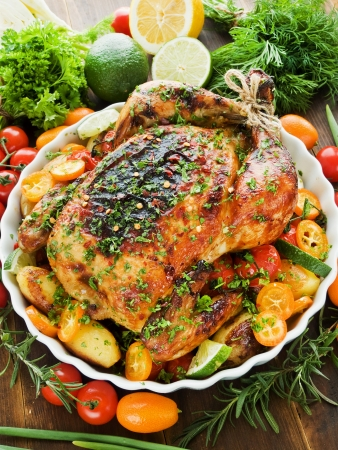 Whole roasted chicken with vegetables, herbs and fruits. Shallow dof. Stock Photo