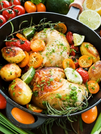 pan fried: Frying pan with roasted chicken, vegetables, herbs and fruits. Shallow dof.