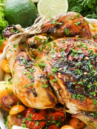 Whole roasted chicken with vegetables, herbs and fruits photo