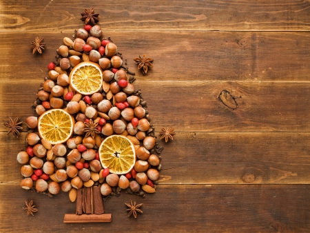 pine nuts: Christmas tree made of nuts, spices and dried oranges  Viewed from above  Stock Photo