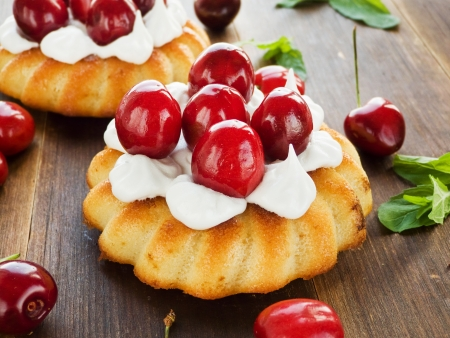 Coconut cakes with whipped cream and sweet cherry. Stock Photo - 20322628