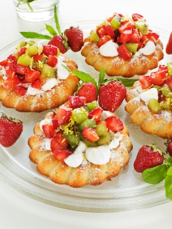 shallow dof: Coconut cakes with whipped cream, strawberry and kiwi. Shallow dof.
