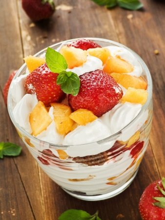 Glass with strawberry-peach parfait and whipped cream. Shallow dof.  photo