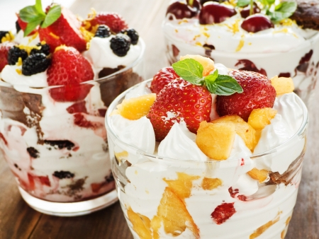 Glasses with berry parfait and whipped cream. Shallow dof.  photo