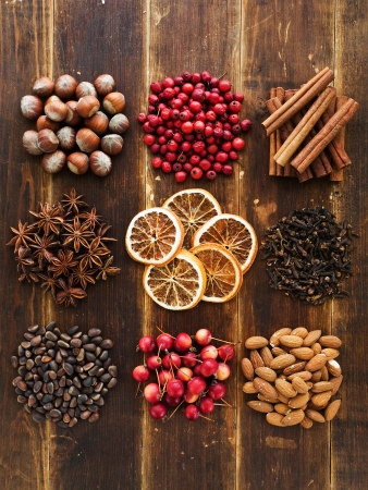 Christmas spices, fruits, nuts and berries on the wooden background. Viewed from above.