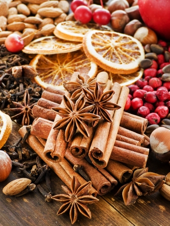ingridients: Christmas spices, fruits, nuts and berries on the wooden background. Shallow dof. Stock Photo