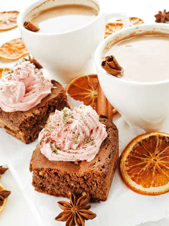 Hot spiced cocoa with milk and chocolate brownies with coconut, red grape whipped cream and mattya. Shallow dof. photo