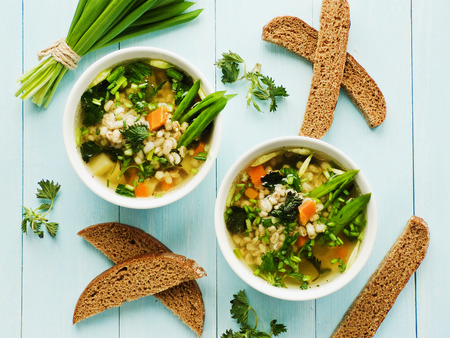 pearl barley: Soup with pearl barley, nettle, carrot and leek. Shallow dof.