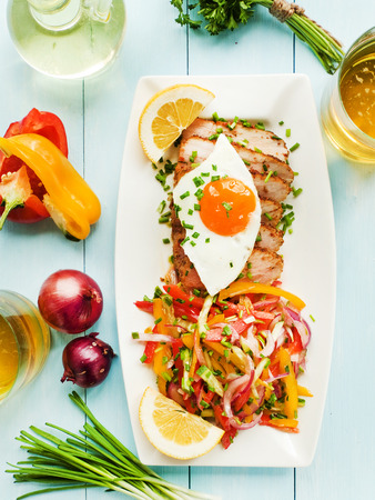 argentinian: Argentinian Asado pork fillet with salad and fried egg. Shallow dof. Stock Photo