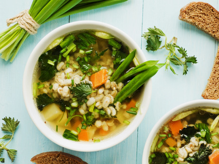 italian bread: Soup with pearl barley nettle carrot and leek. Shallow dof.