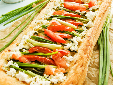 Puff-tart with greens, veggies and cottage cheese. Shallow dof.