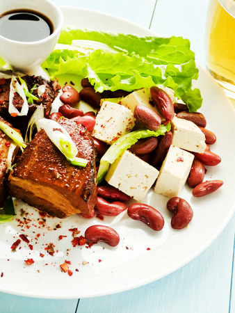 korean salad: Plate with pork ribs, tofu, red beans, herbs and beer. Shallow dof.