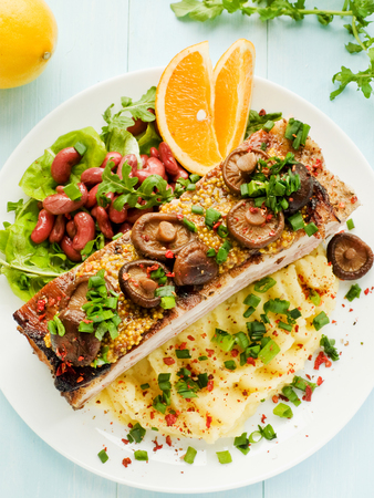 Plate with mashed potatoes, pork ribs, beans and shiitake. Shallow dof.