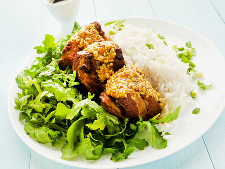 Plate with pork ribs, rice and rucola salad. Shallow dof.