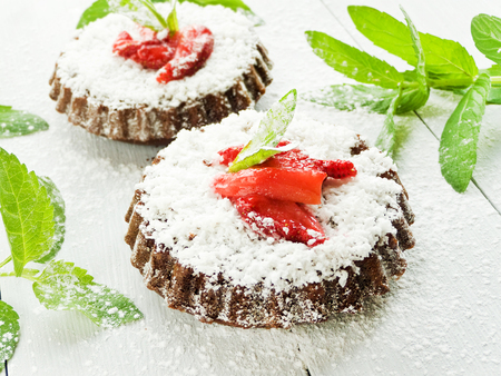Coconut chocolate cakes with strawberry and mint. Shallow dof.
