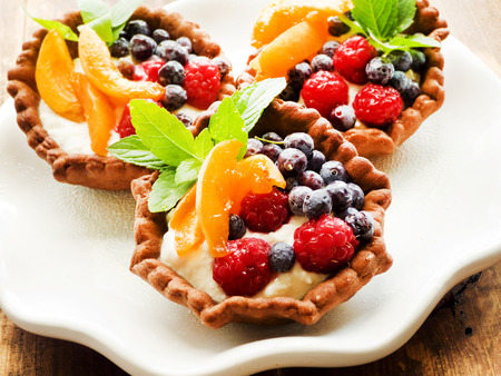 Shortcrust tartlets with cream cheese and berries. Shallow dof.