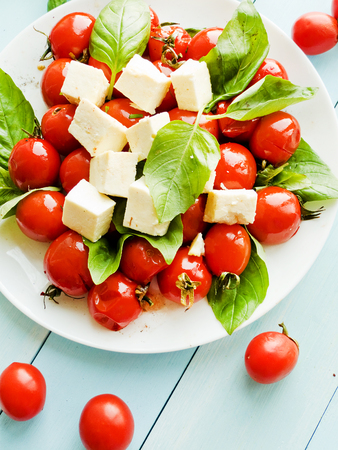 korean salad: Baked cherry tomatoes with greens and cheese. Shallow dof. Stock Photo
