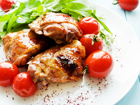 Baked chicken with tomatoes and greens. Shallow dof.