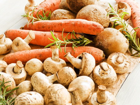 Carrots, champignons and potatoes on wooden background. Shallow dof.