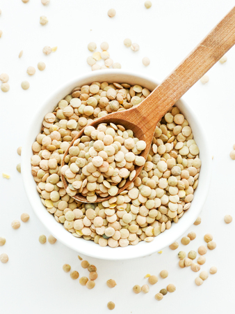 Dry green lentils in a bowl on white wooden background. Shallow dof.