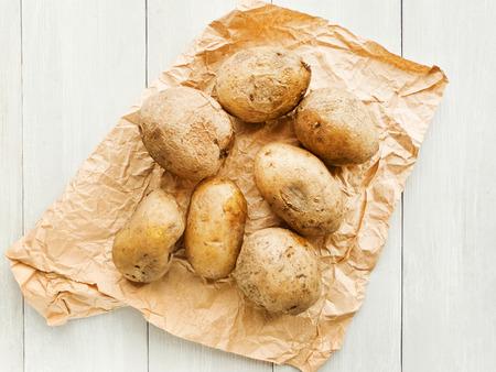 Fresh potatoes on wooden background. Shallow dof. Stock Photo