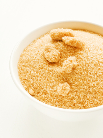 Brown sugar in a white bowl wooden background. Shallow dof.